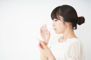 内服薬を服用する若い女性の写真素材 [FYI04655966]