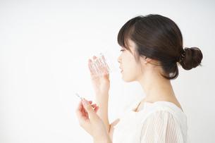 内服薬を服用する若い女性の写真素材 [FYI04655969]