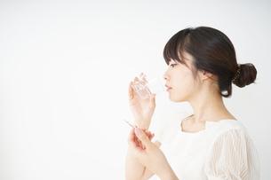 内服薬を服用する若い女性の写真素材 [FYI04655970]