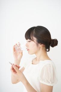 内服薬を服用する若い女性の写真素材 [FYI04655971]