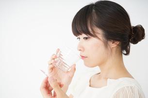 内服薬を服用する若い女性の写真素材 [FYI04655973]