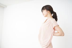 腰の痛みを感じる若い女性の写真素材 [FYI04655991]