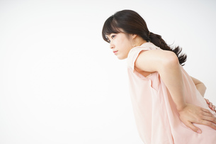 腰の痛みを感じる若い女性の写真素材 [FYI04655993]