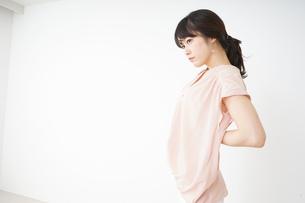 腰の痛みを感じる若い女性の写真素材 [FYI04655994]