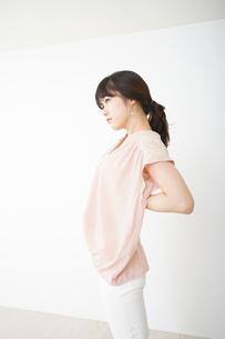 腰の痛みを感じる若い女性の写真素材 [FYI04655998]