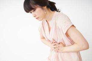 腹痛苦しむ若い女性客の写真素材 [FYI04656010]