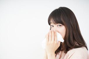 鼻をかむ若い女性の写真素材 [FYI04656043]