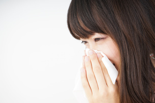 鼻をかむ若い女性の写真素材 [FYI04656044]