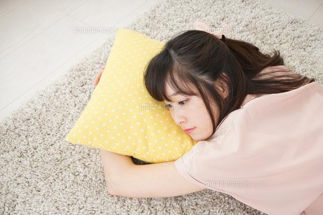 自宅で寝る若い女性の写真素材 [FYI04656109]