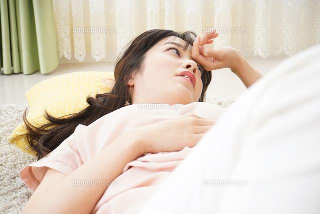 自宅で寝る若い女性の写真素材 [FYI04656119]