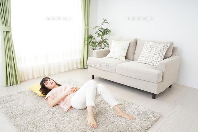自宅で寝る若い女性の写真素材 [FYI04656121]