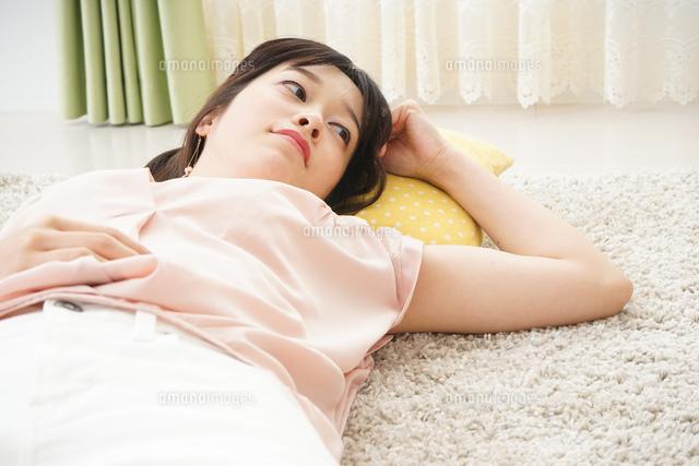 自宅で寝る若い女性の写真素材 [FYI04656131]