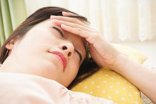 自宅で寝る若い女性の写真素材 [FYI04656134]