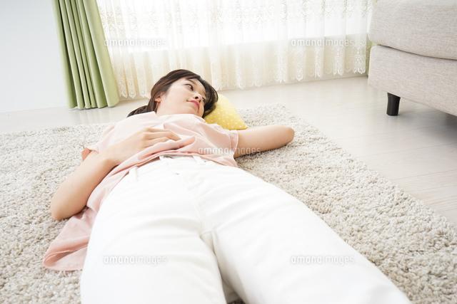 自宅で寝る若い女性の写真素材 [FYI04656138]