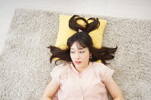自宅で寝る若い女性の写真素材 [FYI04656139]