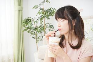 部屋でコーヒーを飲む若い女性の写真素材 [FYI04656145]