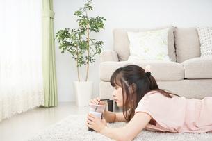 部屋でコーヒーを飲む若い女性の写真素材 [FYI04656152]