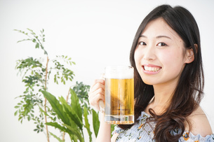部屋でビールを飲む若い女性の写真素材 [FYI04656173]