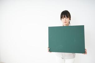 黒板を持つ作業服姿の女性の写真素材 [FYI04656281]