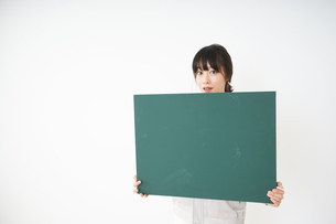 黒板を持つ作業服姿の女性の写真素材 [FYI04656282]