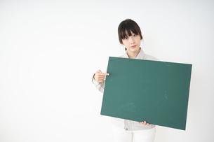黒板を持つ作業服姿の女性の写真素材 [FYI04656283]
