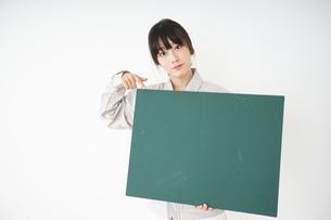 黒板を持つ作業服姿の女性の写真素材 [FYI04656288]