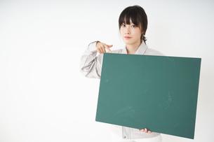 黒板を持つ作業服姿の女性の写真素材 [FYI04656289]