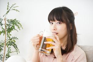 自宅でビールを飲む若い女性の写真素材 [FYI04656383]