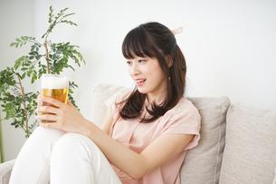 自宅でビールを飲む若い女性の写真素材 [FYI04656390]