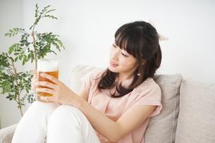 自宅でビールを飲む若い女性の写真素材 [FYI04656393]