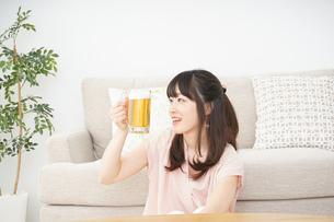 自宅でビールを飲む若い女性の写真素材 [FYI04656397]