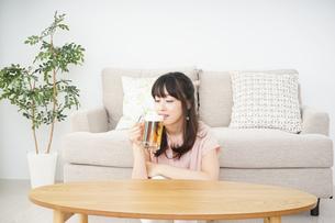 自宅でビールを飲む若い女性の写真素材 [FYI04656399]