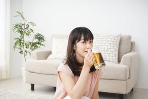 自宅でビールを飲む若い女性の写真素材 [FYI04656408]