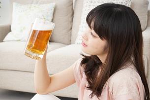 自宅でビールを飲む若い女性の写真素材 [FYI04656415]