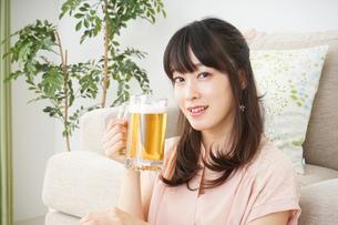 自宅でビールを飲む若い女性の写真素材 [FYI04656419]