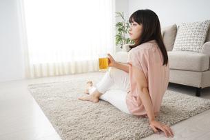 自宅でビールを飲む若い女性の写真素材 [FYI04656420]