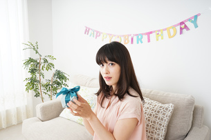 プレゼントを持つ若い女性の写真素材 [FYI04656436]