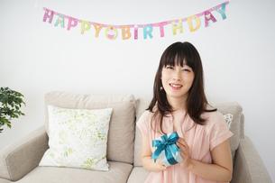 プレゼントを持つ若い女性の写真素材 [FYI04656441]