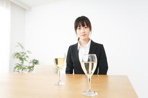 スーツ姿でお酒を飲む若い女性の写真素材 [FYI04656459]