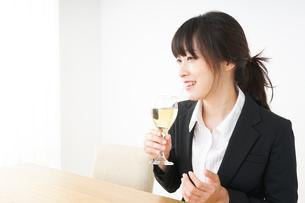 スーツ姿でお酒を飲む若い女性の写真素材 [FYI04656460]