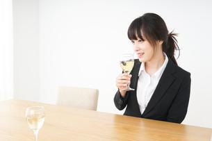 スーツ姿でお酒を飲む若い女性の写真素材 [FYI04656461]