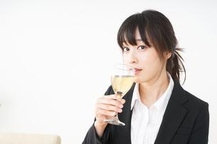 スーツ姿でお酒を飲む若い女性の写真素材 [FYI04656462]
