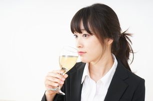 スーツ姿でお酒を飲む若い女性の写真素材 [FYI04656463]
