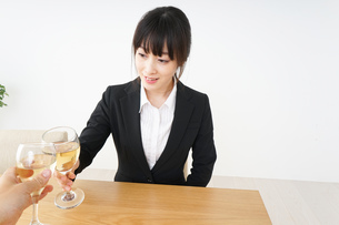 スーツ姿でお酒を飲む若い女性の写真素材 [FYI04656464]