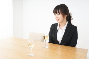 スーツ姿でお酒を飲む若い女性の写真素材 [FYI04656465]