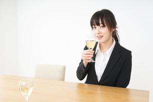 スーツ姿でお酒を飲む若い女性の写真素材 [FYI04656466]