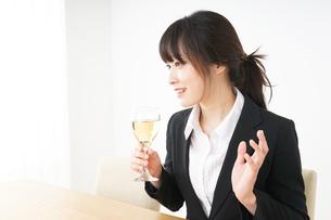 スーツ姿でお酒を飲む若い女性の写真素材 [FYI04656467]