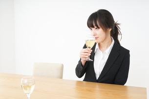 スーツ姿でお酒を飲む若い女性の写真素材 [FYI04656469]