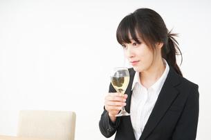 スーツ姿でお酒を飲む若い女性の写真素材 [FYI04656471]
