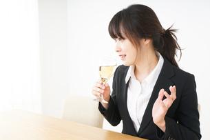 スーツ姿でお酒を飲む若い女性の写真素材 [FYI04656475]